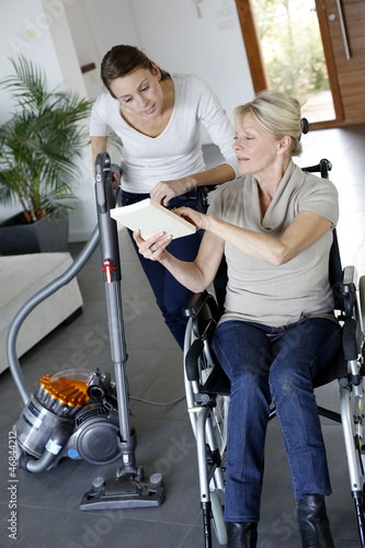 Young woman helping disabled lady at home