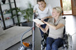 Leinwanddruck Bild - Young woman helping disabled lady at home