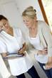 Nurse giving presciption to elderly woman