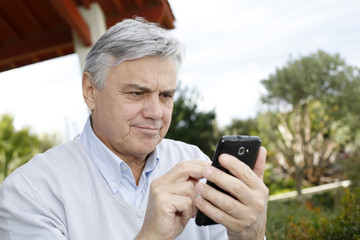 Senior man using smartphone in garden