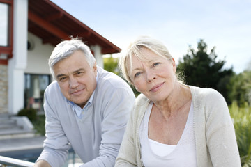 Smiling senior couple standing in home garden