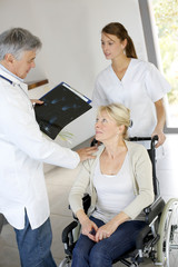 Doctor and nurse talking to patient in wheelchair