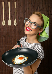 Funny woman cook holding pan with fried egg - close up