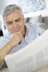 Senior man reading news with perplexed look
