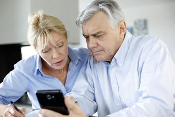 Senior couple calculting bills amount using smartphone