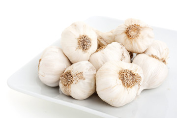 Several head of garlic on the plate, isolated on white backgroun