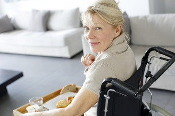 Senior woman in wheelchair holding lunch tray