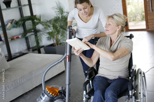 Leinwanddruck Bild Young woman helping disabled lady at home