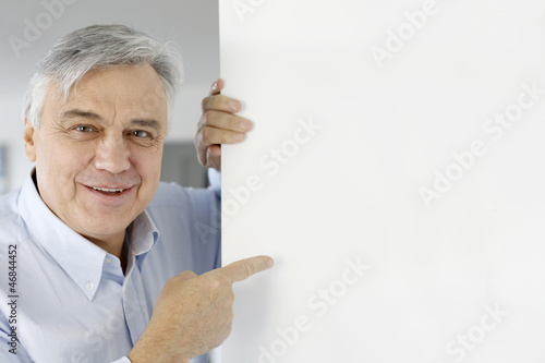 Senior man pointing at message board