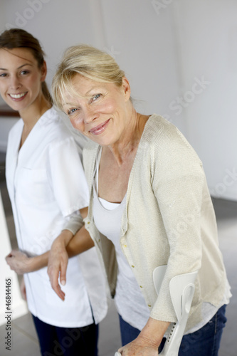 Nurse helping old woman to walk with crutches