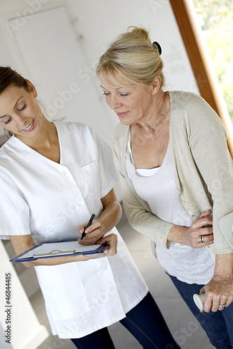 Nurse giving presciption to elderly woman