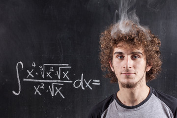 Thinking boy solving equation with smoking head and blackboard