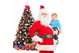 Santa Claus and child posing in front of a decorated christmas t