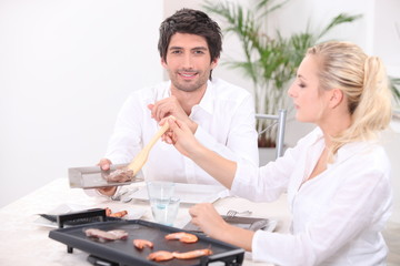 Couple using a table-top grill