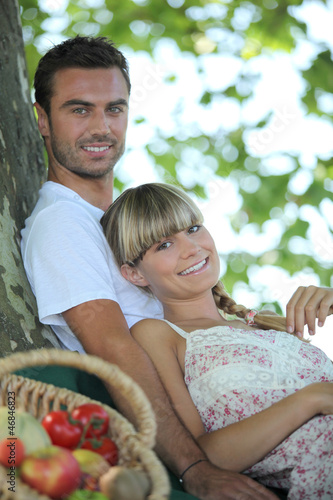 Couple in the field with fruit basket