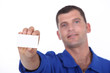 Man in blue overalls holding up a blank business card