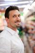 Mann steht im Supermarkt vor einem Regal