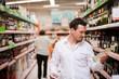 Junger Mann sucht nach Alkohol im Supermarkt