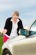 Junge Frau mit Karte auf Auto Motorhaube