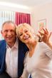 Älteres Paar auf Bett im Hotelzimmer