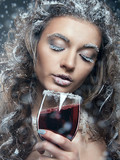 Portrait of young woman with snow make-up with a glass of wine.