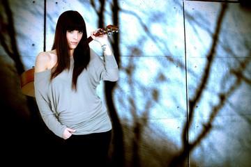 portrait of brunette carrying guitar on her back