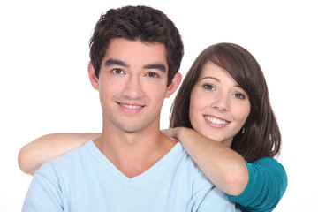 Young couple stood together against white background