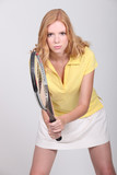 Studio shot of a summery redhead poised with a tennis racquet