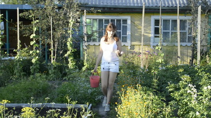 Young woman with a bucket is in the garden