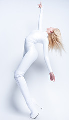 Young blonde in white vinyl suit pointing her finger up