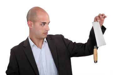 Unenthusiastic businessman holding trowel