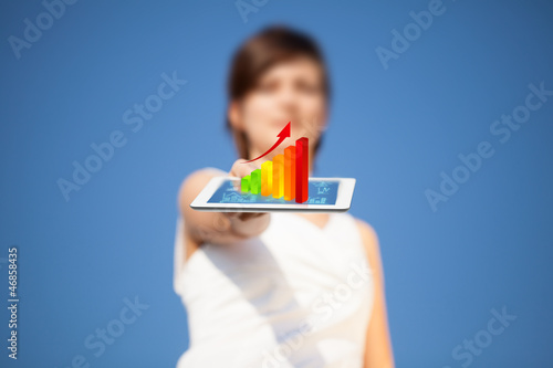 Young woman looking at modern tablet with abstract light and var