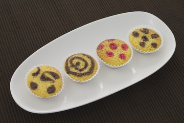 Four small cakes on a plate over a brown towel