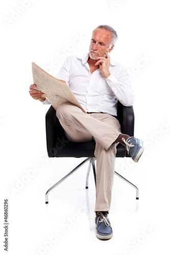 Casual senior man with newspaper, pondering