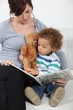 Woman reading a book to little boy on a couch