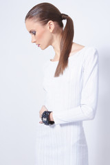 Profile shot of beautiful female model in white dress with amazi