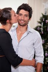 Couple kissing at Christmas
