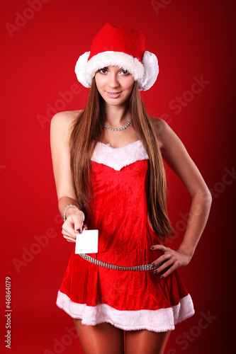 beautiful young brunette woman wearing a Santa's hat holding a b