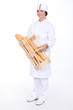 Female baker with baguettes