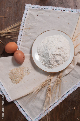 two eggs, flour in plate, til, wheat on light tablecloth