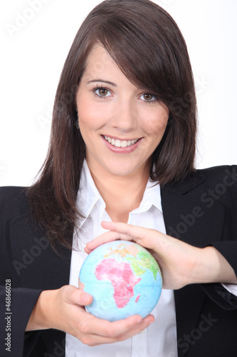 Portrait of a young brown-haired  woman with a globe