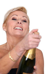 Woman opening bottle of champagne