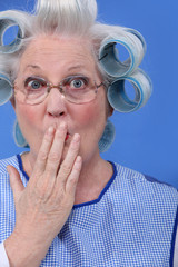 Surprised old woman with her hair in rollers