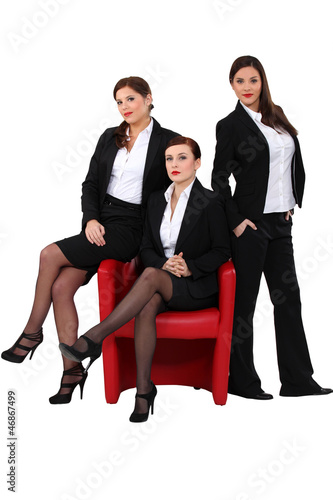 three elegant women in suits posing