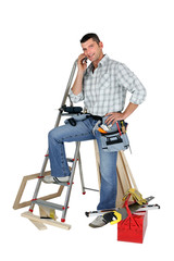 Carpenter stood by equipment making call