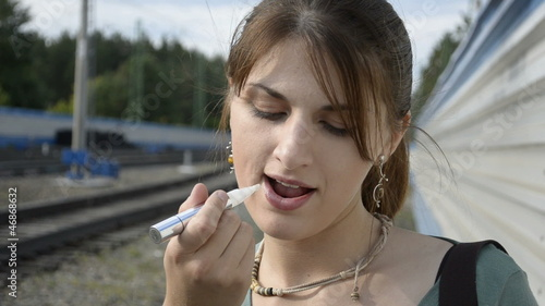 Young woman paints her lips on the railway