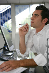Pensive young businessman sat at desk