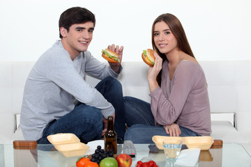 Man and woman eating hamburgers