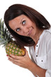 Woman listening to pineapple