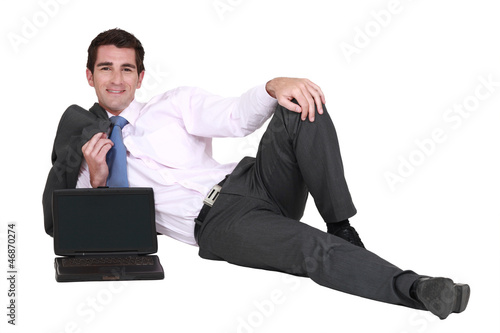 Businessman lying on the floor with his laptop